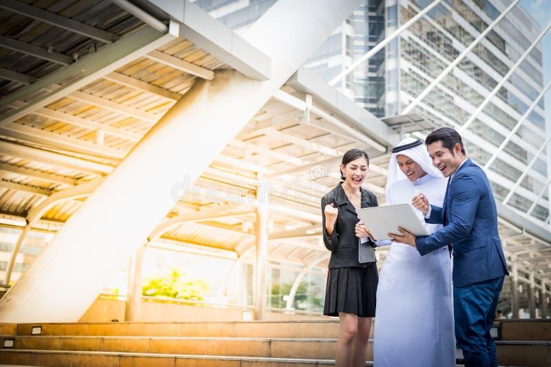 Moslimzakenman en bedrijfsmensen die aan notitieboekje en bespreking over businessplan kijken stock afbeeldingen