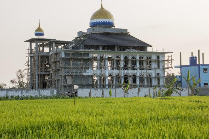 Mosque building construction from rice field stock photo