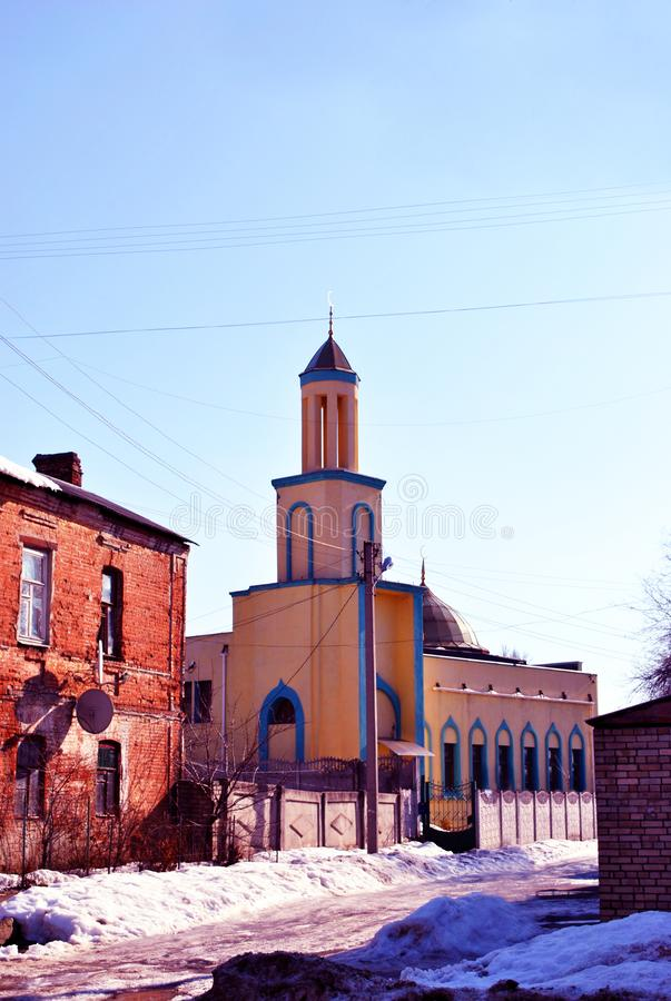Mosque building, soft yellow colors with moons on top, on old city street in winter, red brick building with snow on roof. Blue sky background, Kharkiv royalty free stock images