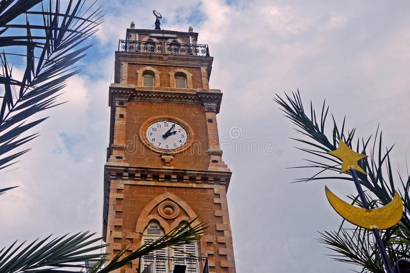 Mosque with a clock against a background of leaves of palm trees and blue sky with clouds in the city of Haifa in Israel. royalty free stock photo