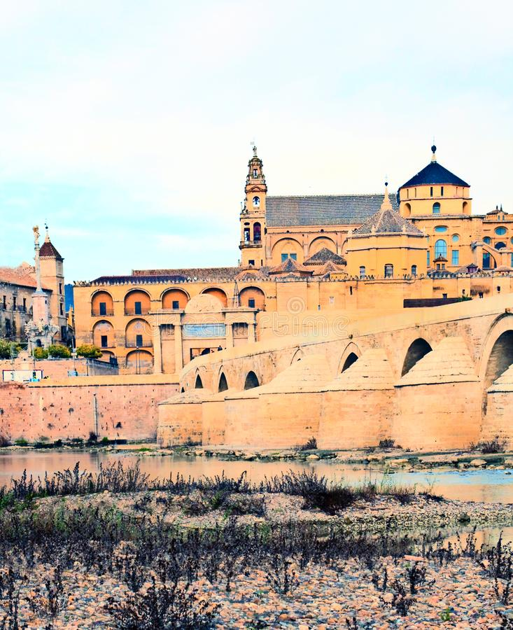 Mosque of Cordoba. Cathedral next to the mosque of Cordoba in the river Guadalquivir in a cloudy day royalty free stock photography