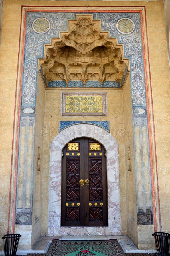 Mosque door in niche with carvings and calligraphy Sarajevo Bosnia Hercegovina. Sarajevo, Bosnia Hercegovina - March 23, 2015: The ornate wood carved door of a stock image