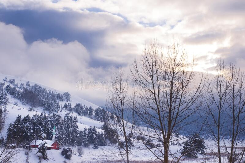 Snow covered mosque on the hill under the winter sky. Mosque on the hill dressed in white under the cloudy cold winter sky in the snow season stock photos