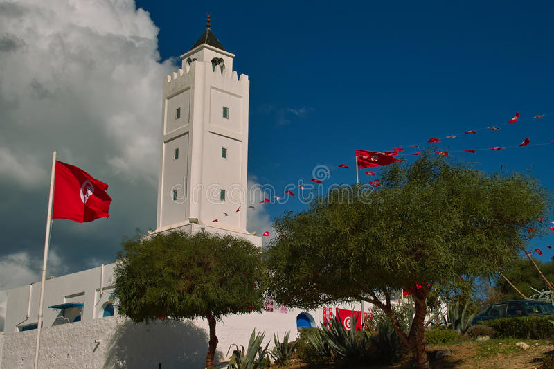 Mosque in Sidi Bu Said. Mosque in Old arabic town in Tunisia Sidi Bou Said, painted white and surrounded by a park and decorated with state flags of Tunisia royalty free stock photo