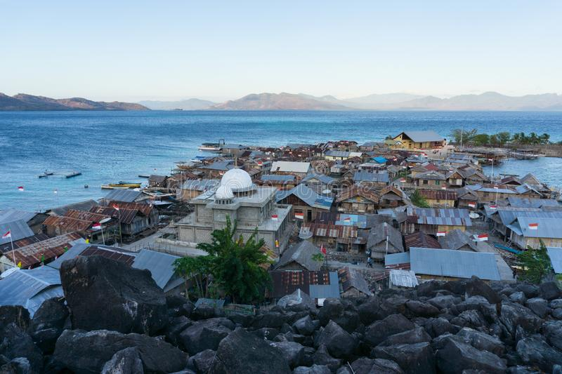 A mosque on a small island north of the island of flores indonesia surrounded by blue seas and black stones and inside it is. Inhabited by dozens of houses royalty free stock photo