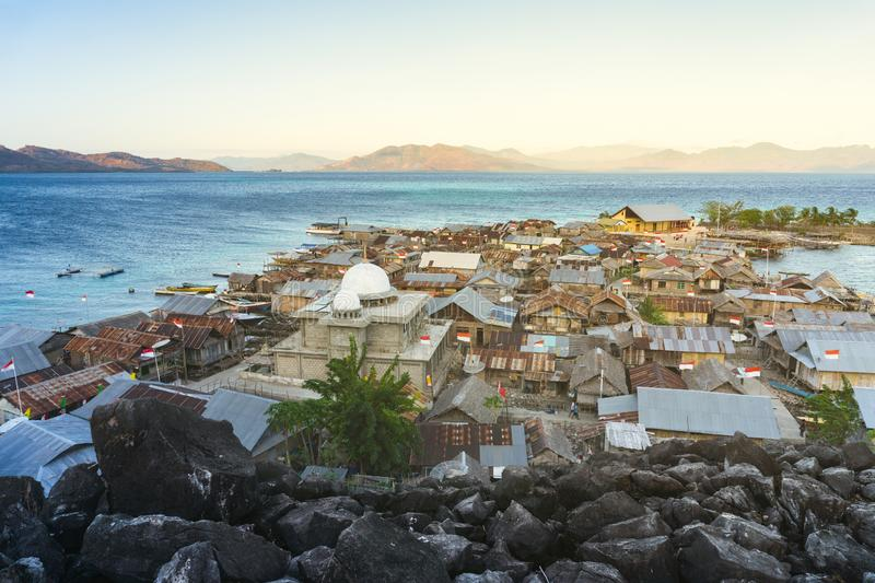 A mosque on a small island north of the island of flores indonesia surrounded by blue seas and black stones and inside it is. Inhabited by dozens of houses royalty free stock image