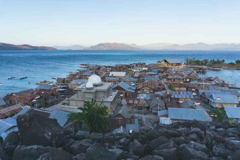 A mosque on a small island north of the island of flores indonesia surrounded by blue seas and black stones and inside it is. Inhabited by dozens of houses stock photography