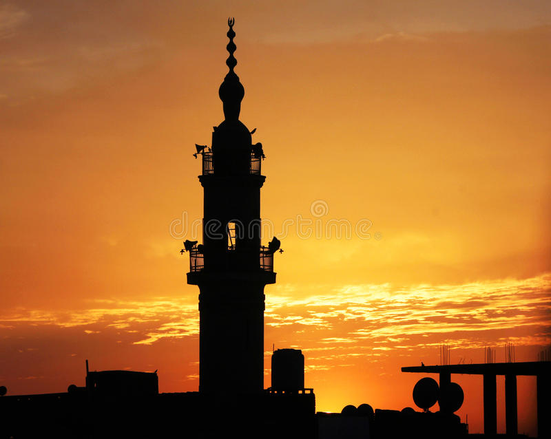 Mosque with sunset in egypt in africa. Minaret of an old mosque with other buildings in silhouette mode during beautiful sunset in an small egyptian city called stock photo