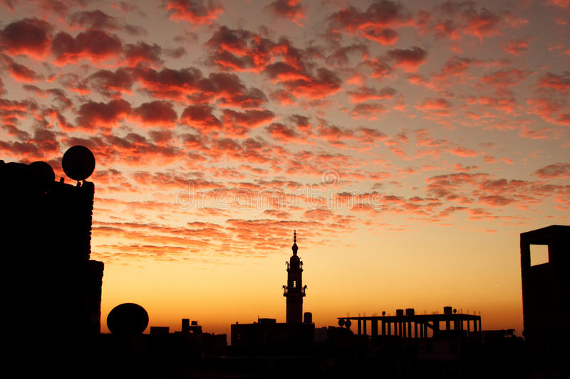 Landscape mosque with sunset in egypt in africa. Minaret of an old mosque with other buildings in silhouette mode during beautiful sunset in an small egyptian stock image