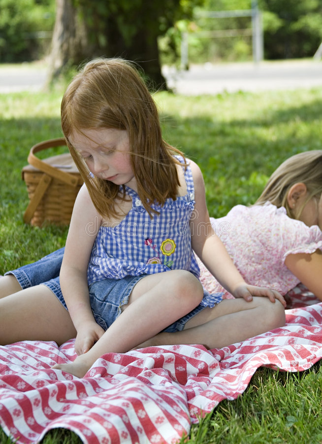Mosquito Bite. Small redhead girl examining a mosquito bite on her ankle. Relaxing after picnic in park stock photos