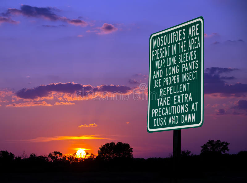 Mosquitoes warning sign. Against beautiful evening sky royalty free stock photo