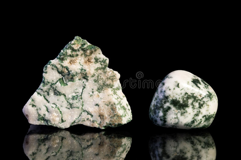 Moss agate, uncut and Tumble finishing. With black background and reflection stock photo