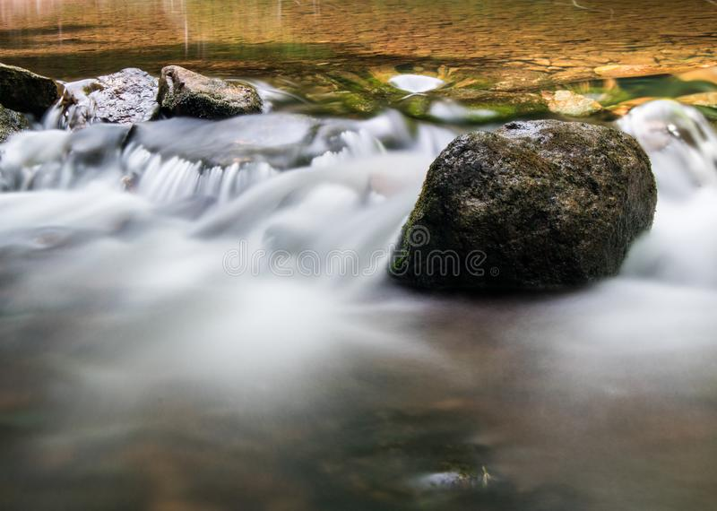 Rock Stands Solid On The Boyne River. A moss covered rock sits solid in the fast moving waters of the Boyne River, just upstream from Hoggs Falls. The location royalty free stock image