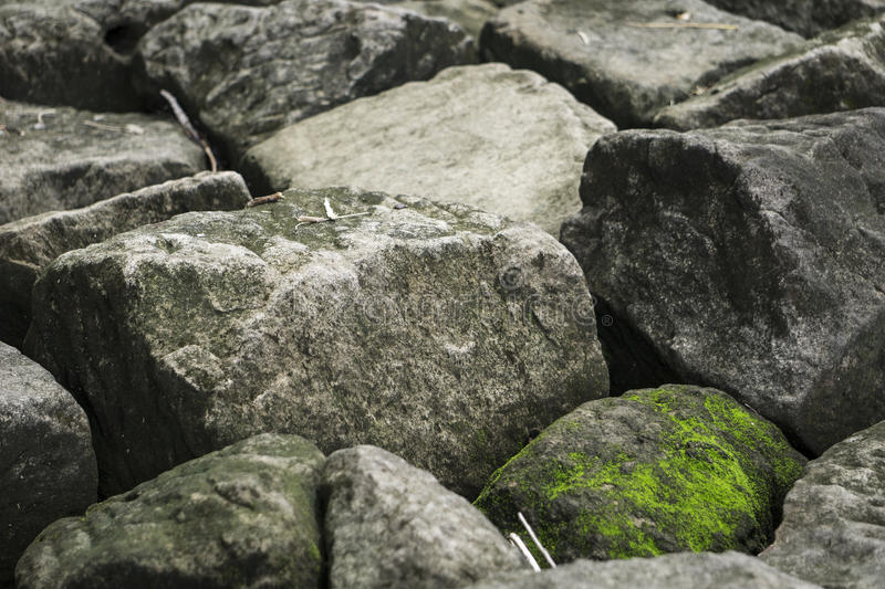 Moss on rock. Natural stone boulders, with sheets of green moss on pieces that are shade protected stock photography