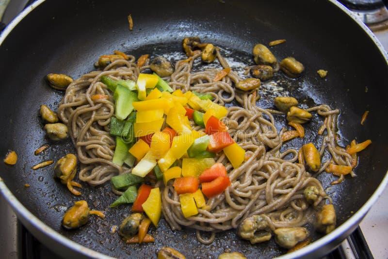 Mosselen en paprika en spaghetti op pan stock fotografie