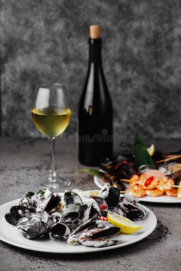 Mosselen in koperpot en witte wijn op steenlijst stock afbeelding