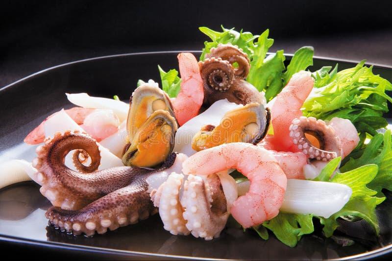mosselen, octopus en calamary in plastiek-waren op zwarte achtergrond royalty-vrije stock afbeelding