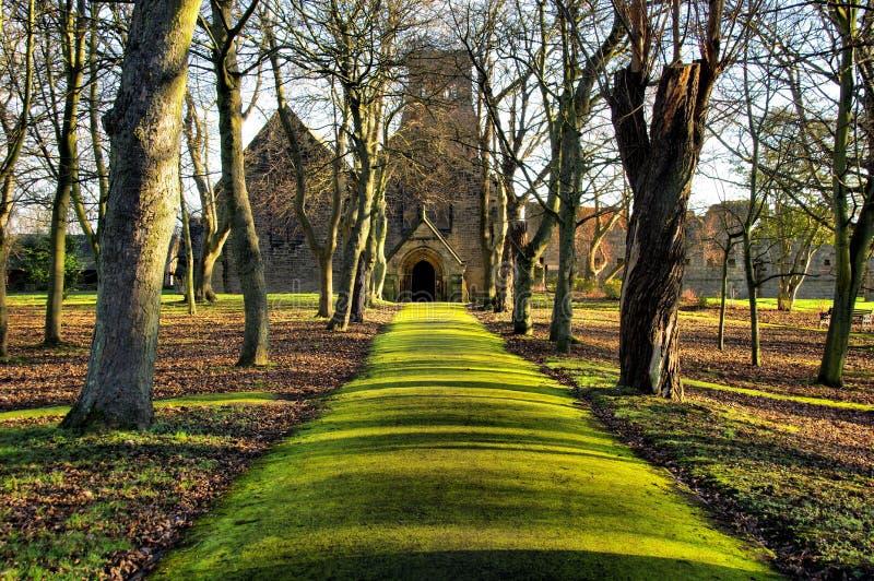 Mossig grön bana till Sts Paul kyrka i Jarrow arkivbilder