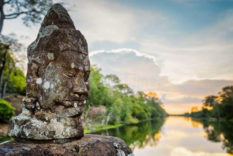 Mossig stenframsida Asura och solnedgång över vallgraven i Angkor, Cambodja royaltyfri bild