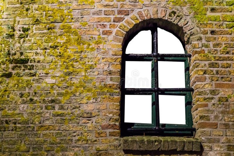 Mossig tegelstenvägg med en gammal träfönsterram, tom ram som isoleras på vit arkivfoton