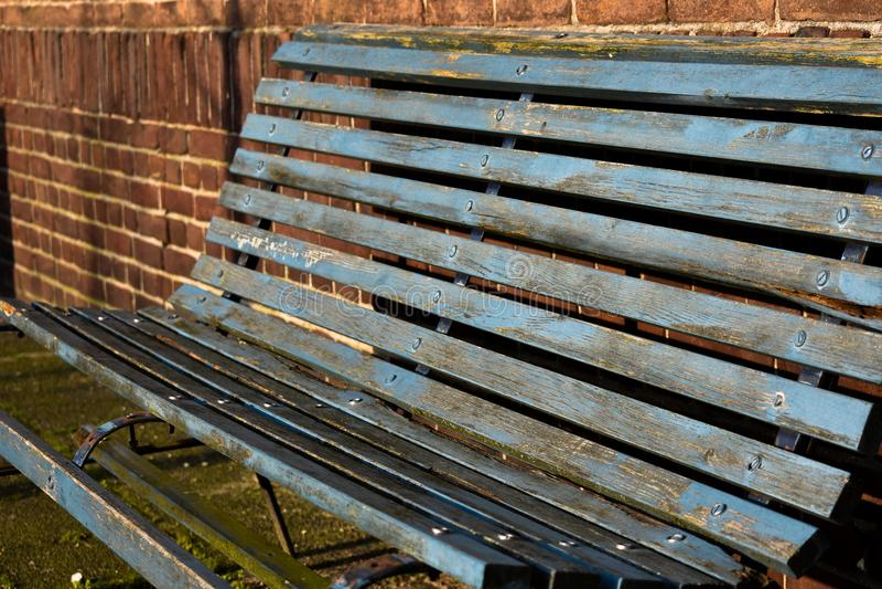 Mossy παλαιός σκουριασμένος κενός απλός πάγκων χάλυβα μετάλλων ξύλινος κάθεται στην μπλε καφετιά ξεπερασμένη αλυσίδα σύσταση στοκ φωτογραφίες
