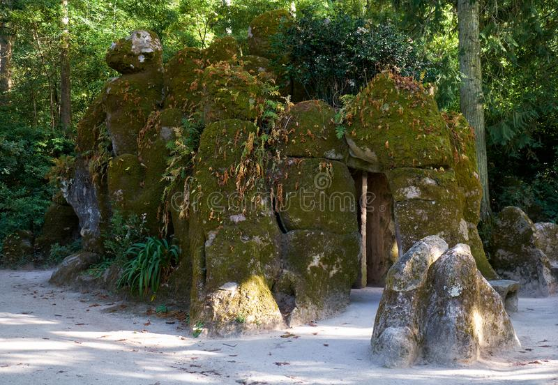 Mossy stones hiding the entrance to Initiation Well in Quinta da Regaleira. Sintra. Portugal. The upper entrance to the Initiation Well (Inverted tower) hided royalty free stock images