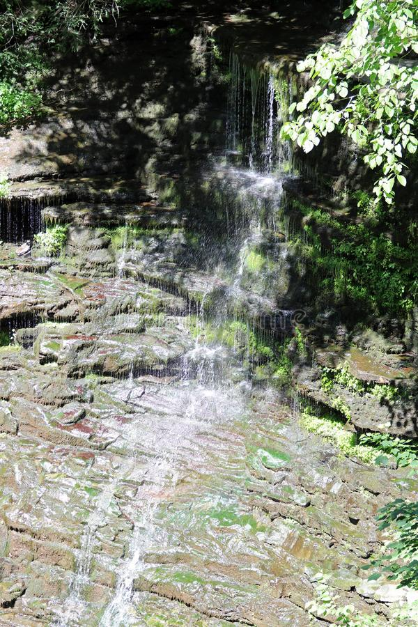 Mossy trickling waterfall. A trickling waterfall flowing over moss covered rocks royalty free stock photos