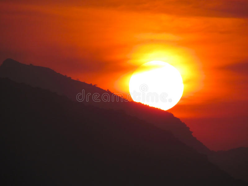 Sunset, setting sun over mountains royalty free stock photography