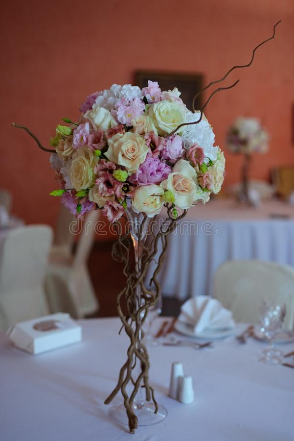 Bouquet of flowers on a leg in the interior of the restaurant for a celebration shop floristry or wedding salon stock image