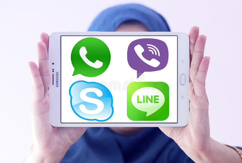 Most famous messenger applications logos. Arab muslim woman holding white tablet and most popular messenger applications logos on display royalty free stock photography