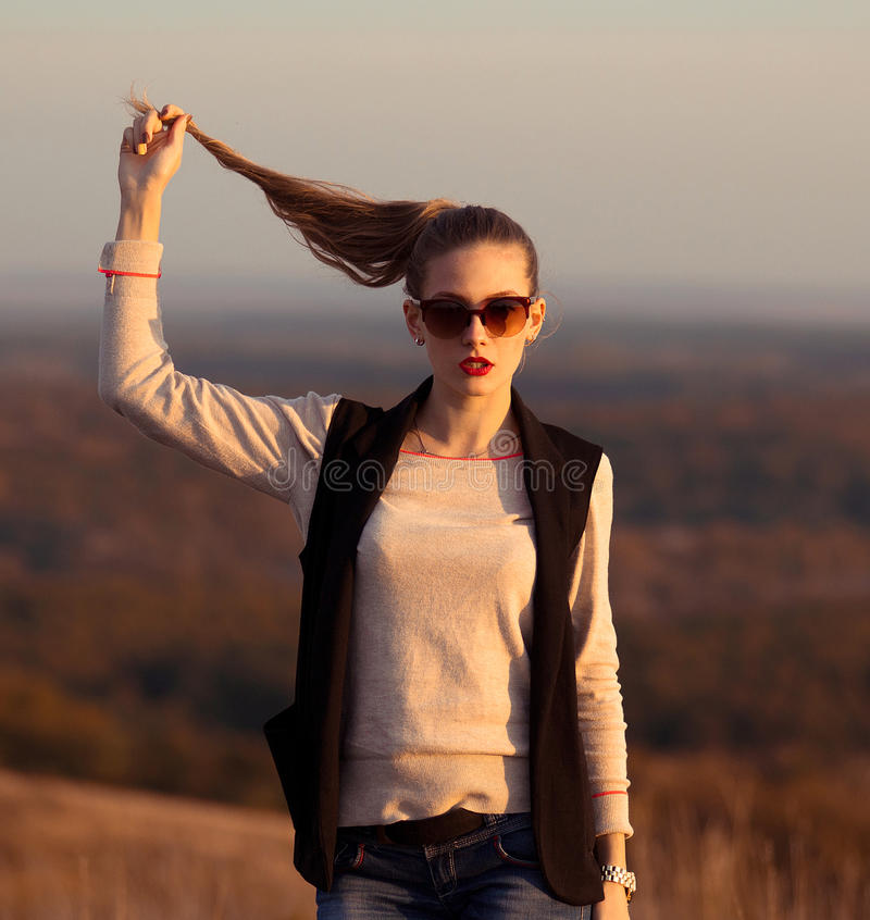 Fashionable,glamorous model stand on hills and held ponytail.Attractive,beautiful girl with sunglasses look at sunset. stock image