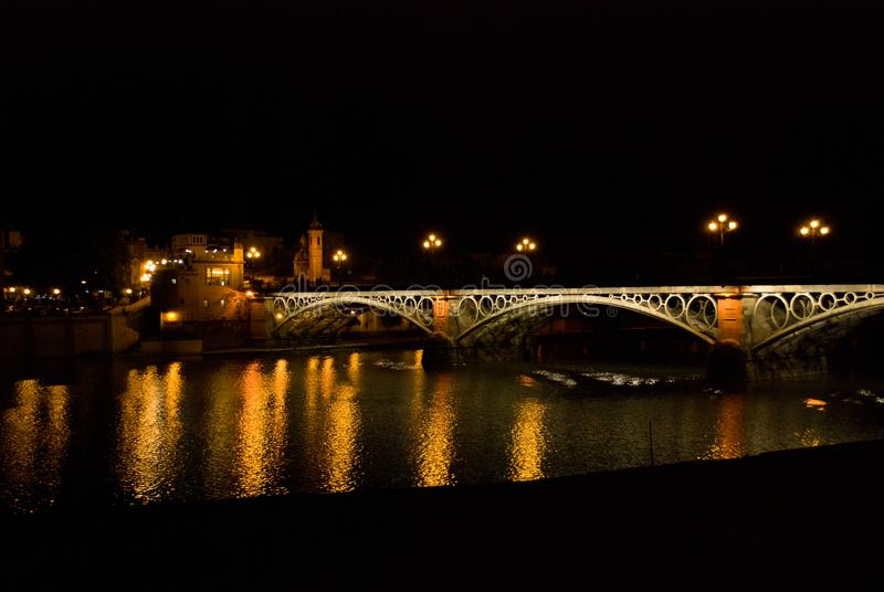 The night in Seville, Spain, reflections on the Guadalquivir river in the popular neighborhood of Triana. The most `important square in Seville royalty free stock photo