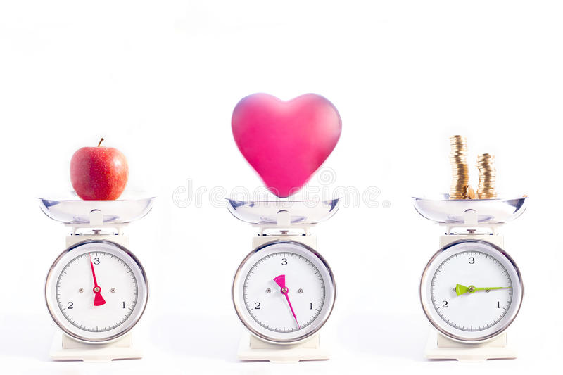 The most important things in life: health, love and money. An Apple, balloon and money is weighed on scales isolated on white. Concept of health, love and money royalty free stock photos