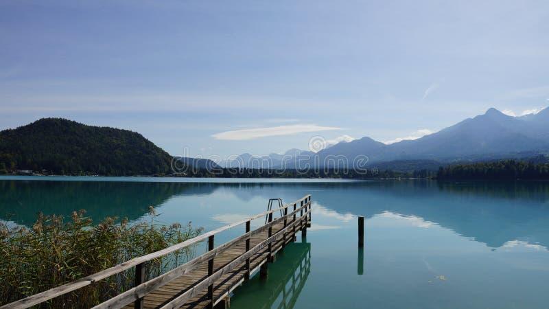 Most na jeziornym Faaker z widokami górskimi obrazy royalty free