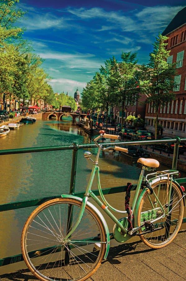Most na kanale z rowerem wtykał przy balustradą i cumował łodzie pod niebieskim niebem w Amsterdam obrazy royalty free