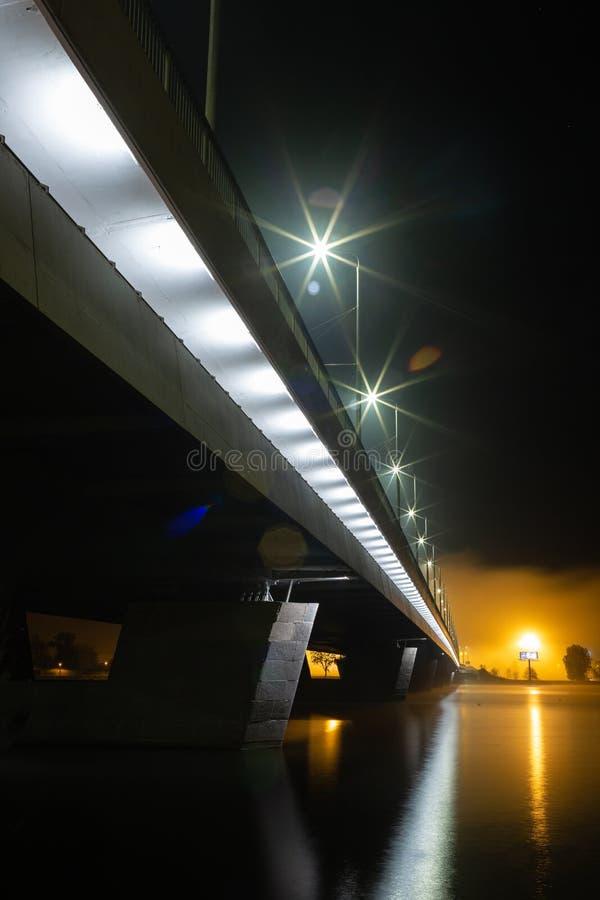 Most nad Daugava rzeką w Ryskim, Latvia miasto światła na noc fotografia stock