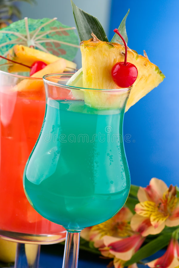 Most popular cocktails series - Blue Hawaiian and. Blue Hawaiian and Hurricane cocktails surrounded by tropical fruits. Most popular cocktails series stock photo