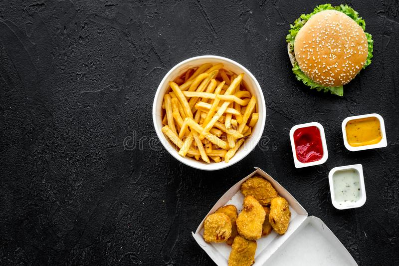 Most popular fast food meal. Chiken nuggets, burgers and french fries on black background top view copy space royalty free stock photography