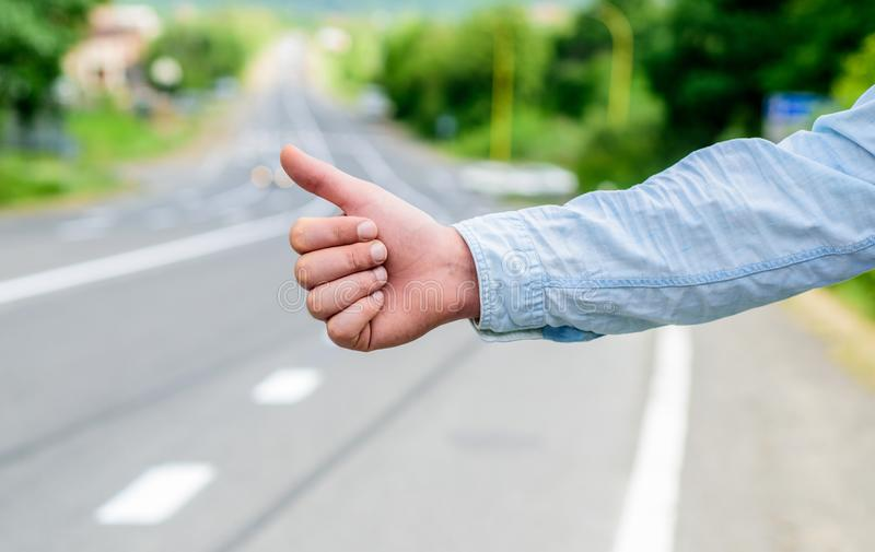 Most popular way of hitchhiking is to thumb up. Hand thumb up gesture try stop car road background. Thumb or hand. Gesture hitchhiking. Make sure you know right royalty free stock photos