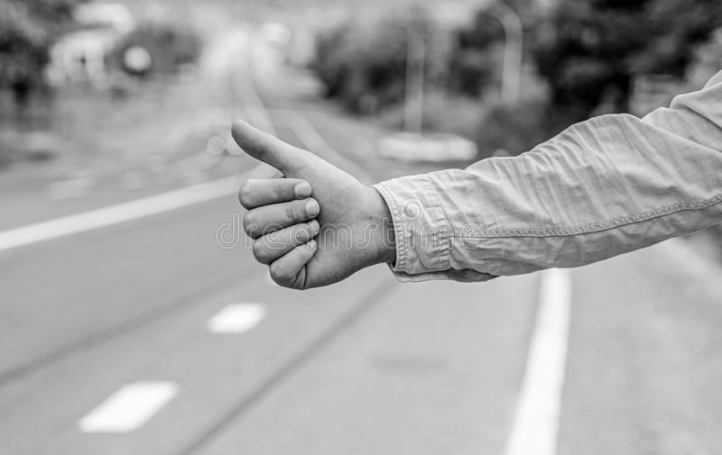 Most popular way of hitchhiking is to thumb up. Hand thumb up gesture try stop car road background. Thumb or hand stock images