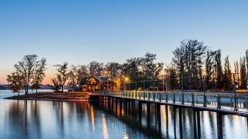 Most prowadzi wyspa z drewnianymi chałupami iluminować wieczór iluminacją Wieczór scena obraz royalty free