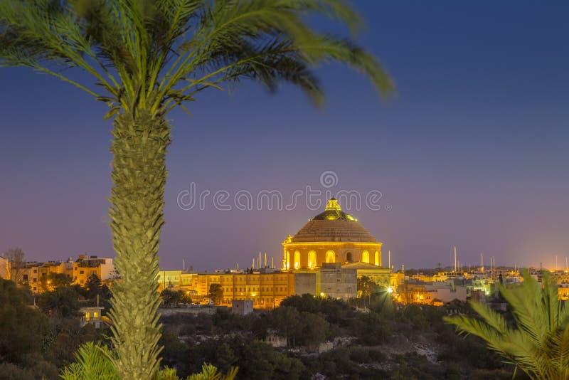 Mosta Malta - den Mosta kupolen med palmträdet vid natt royaltyfri bild