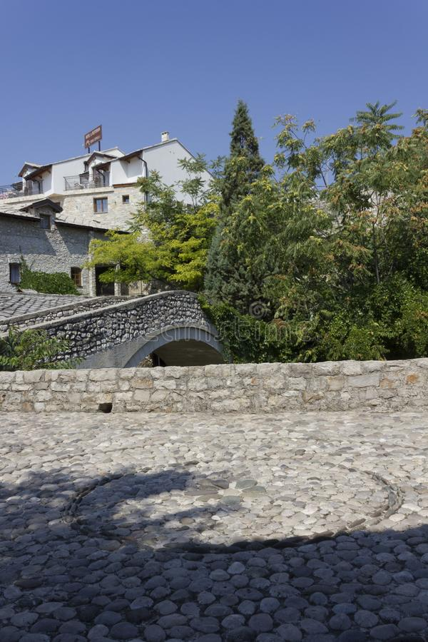 Ancient cobblestone square in Mostar. MOSTAR, BOSNIA AND HERZEGOVINA - AUGUSt 17 2017: Ancient cobblestone square in Mostar near an old stone bridge, nobody royalty free stock photo