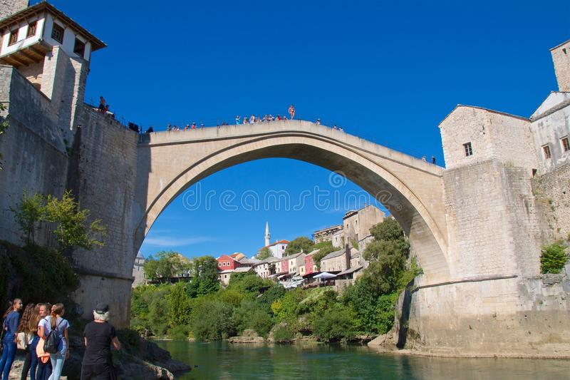 Mostar, Bosnia & Herzegovina - October 2017: Tourists watch a man jumping from the famous old bridge over Neretva River in Mostar, stock image