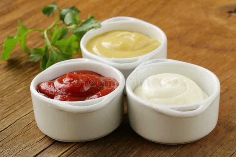 Mostarda, ketchup e maionese - três molhos dos tipos fotografia de stock royalty free