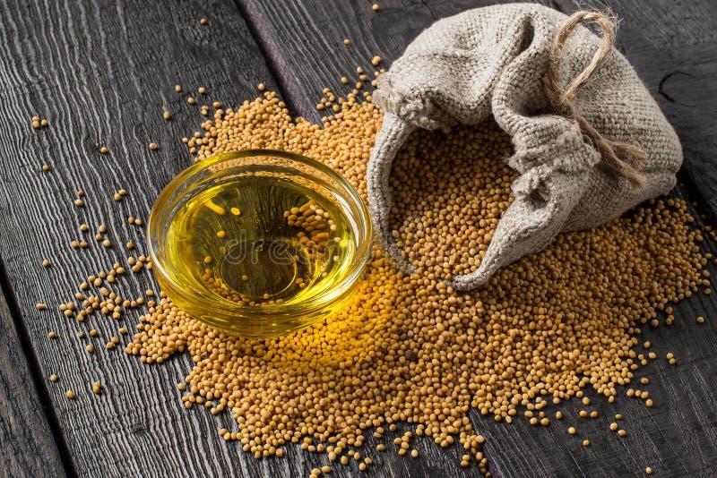 Mostaza del grano en el aceite del bolso y de mostaza en el cuenco fotos de archivo