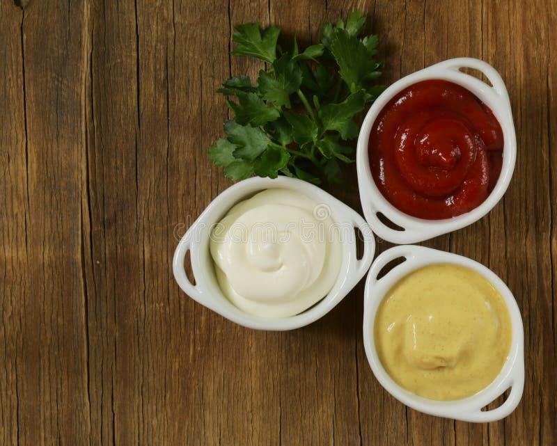 Mosterd, ketchup en mayonaise - drie soortensausen stock foto's