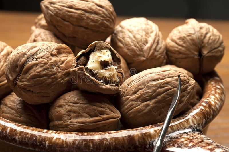 Mostly unshelled walnuts in bowl. A group of mostly unshelled walnuts and a pick royalty free stock image