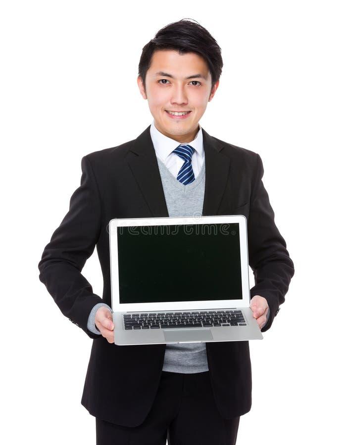 Mostra asiática do homem de negócios com laptop fotografia de stock royalty free