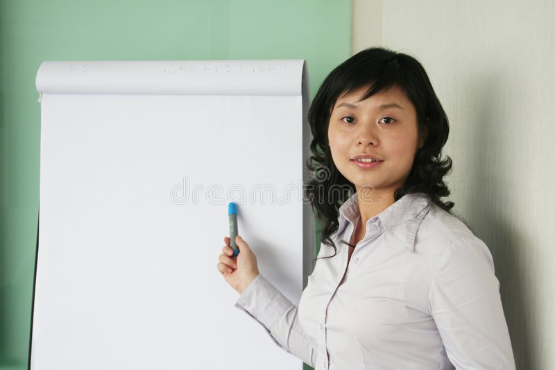 Mostra asiática nova das mulheres antes do whiteboard foto de stock